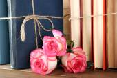 Tied books with pink roses — Stock Photo