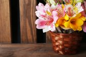 Beautiful flowers in vase on wooden background — Stok fotoğraf