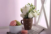 Delicious macaroon with beautiful flowers on light background — Stock Photo