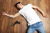 Crime scene simulation, young man lying with gun on floor — Stock Photo
