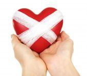 Female hands holding bandaged heart isolated on white — Stock Photo