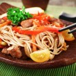 Chinese noodles with vegetables and roasted meat on bamboo mat background — Stock Photo #73830083