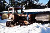 Old broken tractor over snow in wintertime — Stock Photo