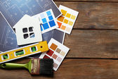 Color samples, decorative house, gloves and paintbrushes — Stock Photo
