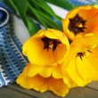 Beautiful yellow tulips with napkin on wooden table, closeup — Stock Photo #73914703