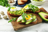 Tasty sandwiches with egg, avocado and vegetables on wooden background — Stock Photo