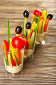 Snack of vegetables in glassware on wooden background — Stock Photo
