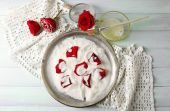 Making candied rose flower petals with egg whites and sugar, on wooden background — Stock Photo