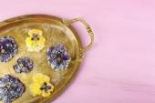 Candied sugared violet flowers on tray, on color wooden background — Stock Photo