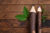 Wooden pencils with leaf on wooden background — Stock Photo