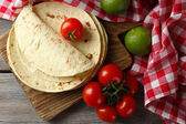 Stack of homemade whole wheat flour tortilla and vegetables on cutting board, on wooden table background — Stock Photo