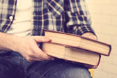 Young man holding books, close-up — Stock Photo