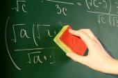 Teacher hand wiping off formulas on blackboard background — Stock Photo