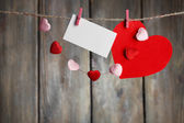 Bright hearts and card hanging on rope on wooden background — Stock Photo