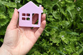 Female hand holding toy house outdoors — Stock Photo