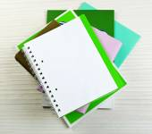 Notebook on top of pile of books and magazines on wooden background — Stock Photo