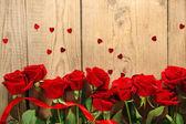 Hermosas rosas en mesa de madera vieja — Foto de Stock