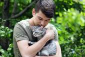 Handsome young man with cute cat outdoors — Stock Photo