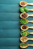 Wooden spoons with fresh herbs and spices on color wooden background — Stock Photo