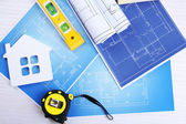 Construction instruments, plan and brushes over house plan on wooden table background — Stock Photo