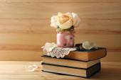 Fresh roses with old books on  wooden background. Vintage concept — Stock Photo