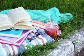Książki, okulary i pić na szczegół trawa — Zdjęcie stockowe