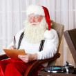 Santa Claus sitting with list of children wishes in comfortable chair at home — Stock Photo #74316237