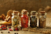 Assortment of spices in glass bottles on wooden background — Stock Photo