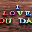 Inscription I LOVE YOU DAD made of colorful letters on wooden background — Stock Photo #74366057