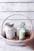 Milk in glassware with walnuts and cookies on wooden background — Stock Photo