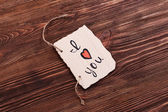 Inscription I LOVE YOU on cutout carton on wooden background — Stock Photo
