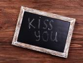 Inscription KISS YOU on blackboard on wooden background — Fotografia Stock