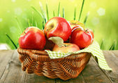 Wicker basket of red apples with napkin on bright background — Stock Photo