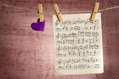 Bright heart and music sheet hanging on rope on wooden background — Stock Photo