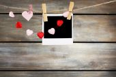 Bright hearts and photo paper hanging on rope on wooden background — Stock Photo