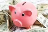 Piggy bank on pile of dollars, closeup — Stock Photo
