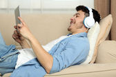 Handsome young man lying on sofa and listening to music in room — Stock Photo