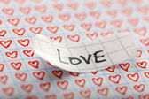 Word LOVE written on torn paper on heart background — Stock Photo