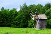 Old wooden windmill on green field, on forest and blue sky background — Stock Photo