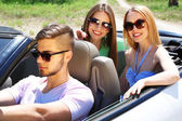 Three friends in cabriolet, outdoors — Stock Photo