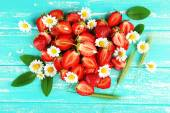 Strawberry with chamomile, leaves and ears in shape of heart on color wooden background — Stock Photo