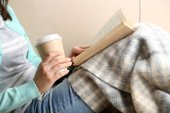 Young woman reading book, close-up, on home interior background — Stock Photo