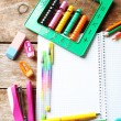 Notebook and bright school stationery on old wooden table — Stock Photo #74668733