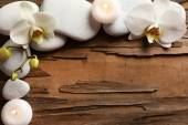 Spa stones and orchid flower on wooden background — Stock Photo