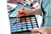 Female makeup artist with cosmetics at work close-up — Stock Photo