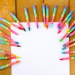 Colorful pastel crayons with white sheet of paper on wooden table, top view — Stock Photo #74672579