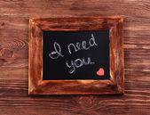 Inscription I NEED YOU on blackboard on wooden background — Stock Photo