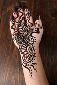Hand painted with henna on wooden background — Stock Photo