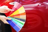 Female hands with paint samples choosing color for painting car, closeup — Stock Photo