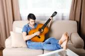 Young man with guitar on sofa in room — Stock Photo